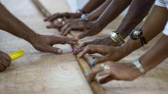 "Workers help Cuban cigar roller Jose ""Cueto"" Castelar, hand roll a 90-meter cigar, in Havana, Cuba, Friday, Aug. 12, 2016."