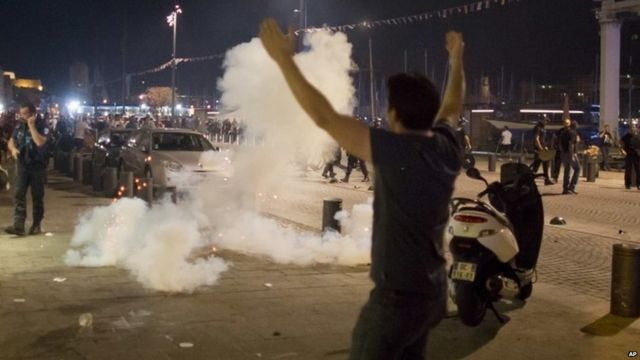 Man walking in front of teargas cloud used by police following scuffles in Marseille on 10 June