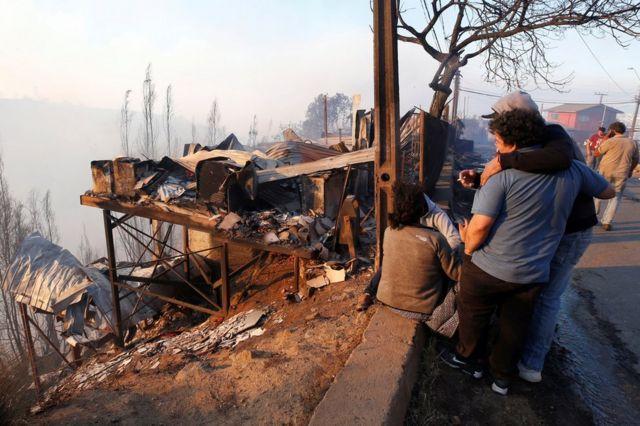 주민들이 불탄 집의 흔적들을 보고 있다