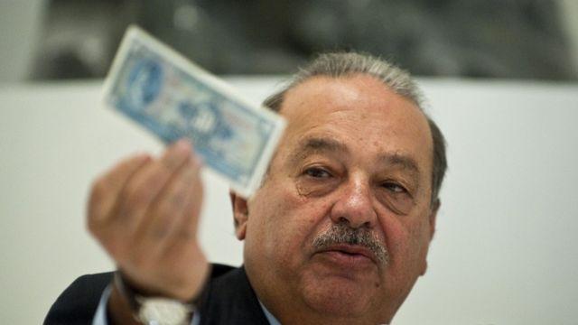 Carlos Slim muestra un billete.