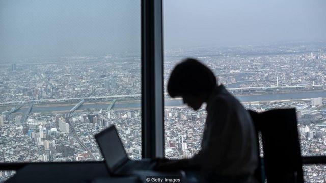 Homem trabalhando na penumbra