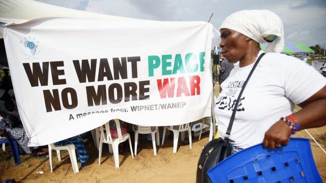 """Una mujer liberiana pasa frente a un cartel de """"Queremos paz, no más guerra""""."""