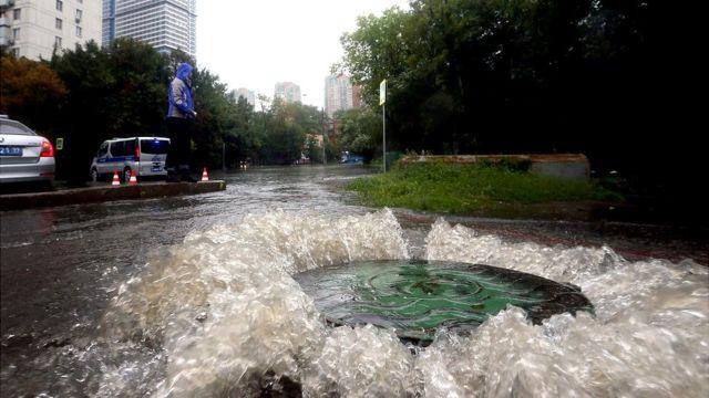Вода, бурлящая у люка на московской улице