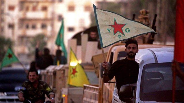 Hombre sosteniendo una bandera con las iniciales de las YPG.