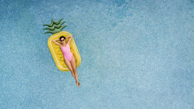 Carefree woman on inflatable pineapple, floating on a beautiful turquoise swimming pool