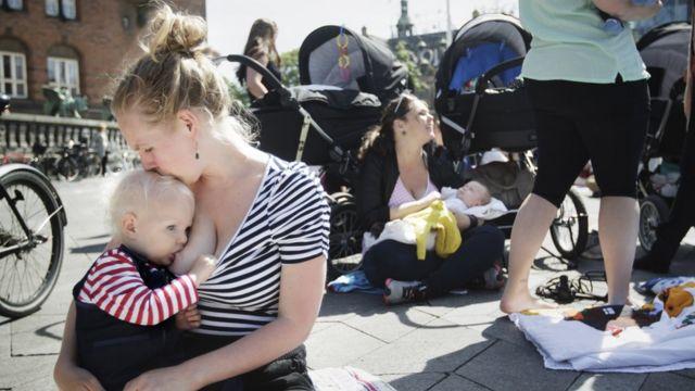 Mujer amamantando a un bebé.
