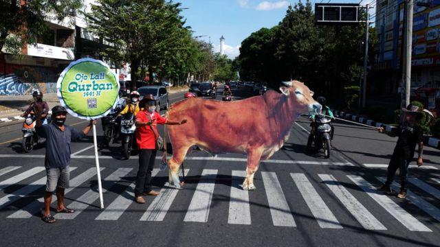 Sejumlah relawan membawa replika sapi saat aksi kampanye berkurban di Jalan Slamet Riyadi, Solo, Jawa Tengah, Rabu (29/7/2020). Aksi itu digelar untuk mengajak masyarakat melaksanakan ibadah berkurban di Hari Raya Idul Adha 1441 H.