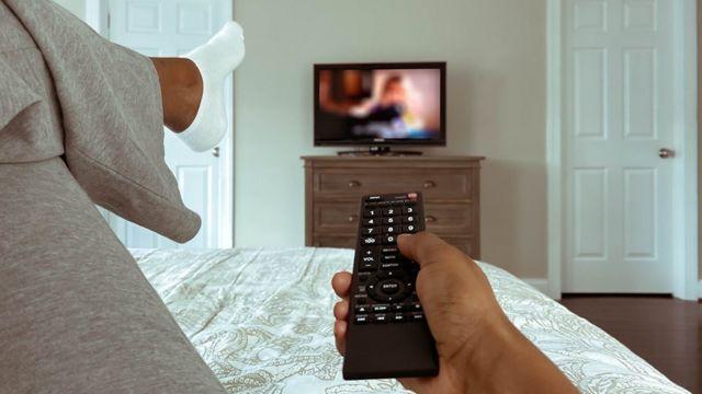 Mulher vendo televisão da cama