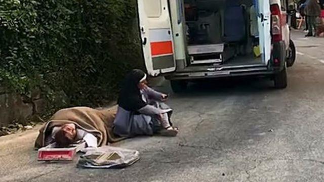 La monja Mariana sentada fuera de su convento destruido