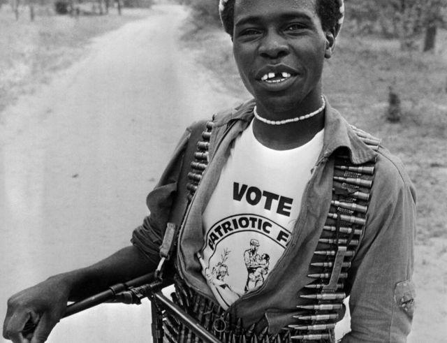 Mpiganaji aliyeunga mkono vugu vugu Patriotic Front akiwa amebeba risasi na bunduki aina ya machine gun, akitabasamu wakati wa uchaguzi mkuu mwezi Machi 04, 1980 katika kampbi ya Lupane