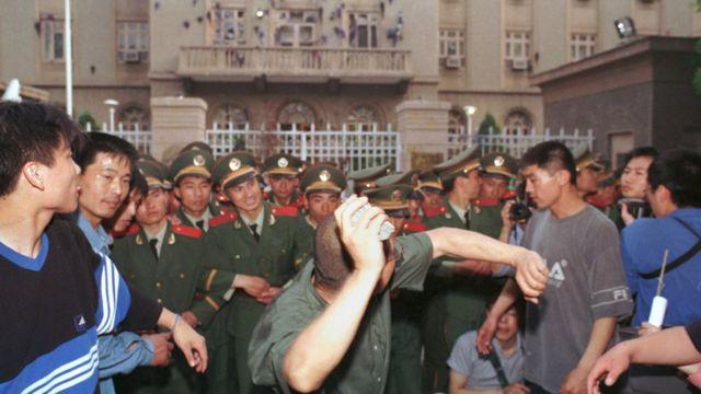 Jedan od studenata baca kamen na ambasadu Amerike u Pekingu, 9. maja 1999. Protesti su izbili u desetak većih gradova u Kini i izvukli desetine hiljada besnih građana na ulice. Kineski državni mediji su podgrejali bes govoreći da je NATO bombardovanje ambasade u Beogradu bio namerni čin agresije.