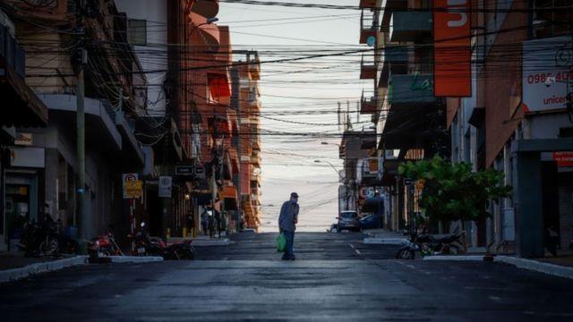 Homem atravessa rua vazia, rodeada de prédios