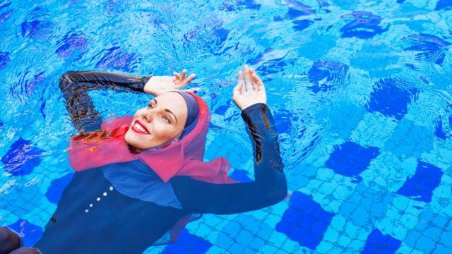Mulher na piscina com um burkini e véu
