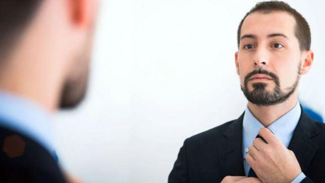 Un hombre se acomoda la corbata frente al espejo.