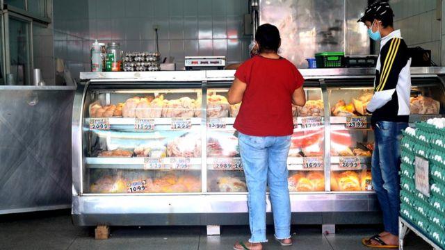 Lindinalva comprando carcaças e pele de frango ao lado do neto dela