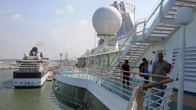 Tourists walk on deck of a cruise ship anchored in Colon, some 100 km north of Panama City on December 7, 2008.