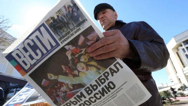Hombre lee un periódico celebrando la anexión de Crimea