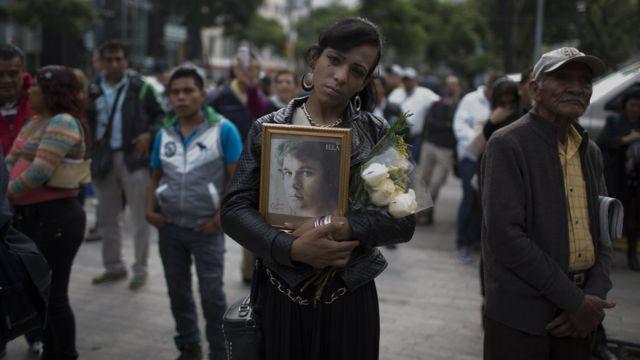 Una joven sostiene una fotografía de Juan Gabriel.
