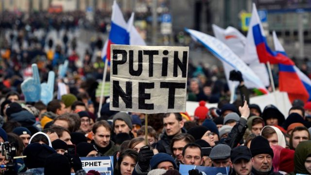 """A protester holds a placard reading """"Putin - No!"""" during an opposition rally in central Moscow, on 10 March"""