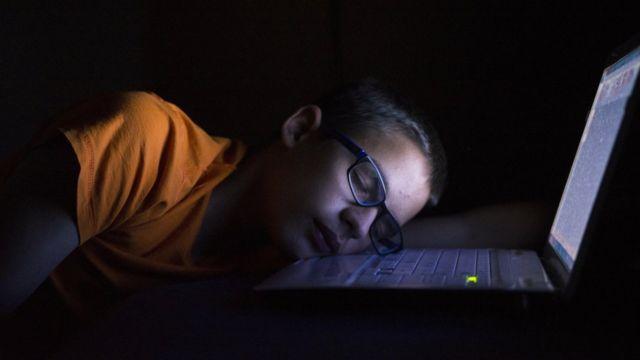 Menino dormindo em frente ao laptop