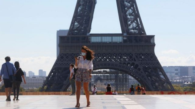 A woman in a face mask walks in front of the Eiffel Tower in Paris