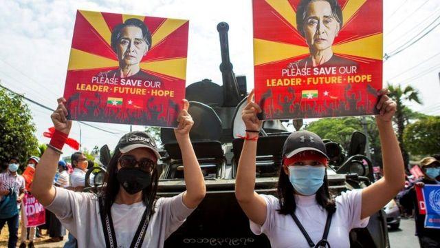 فتاتان ترفعان صورة لزعيمة البلاد أونغ سان سو تشي امام عربة مدرعة فيا مدينة يانغون