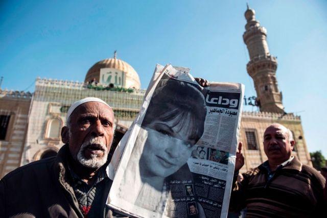 """رجلان مصريان يحمل أحدهما صحيفة بها صورة لشادية وعنوان يقول """" وداعا معبودة الجماهير."""