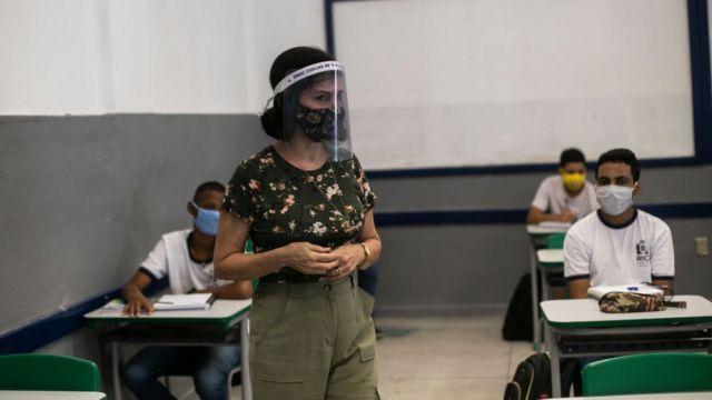 Professora em pé com máscara e protetor facial. Alunos, que estão sentados, usam mácaras e uniforme.