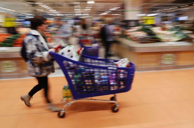 Mujer con carrito en supermercado.