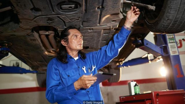 Homem conserta carro