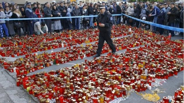 A Romanian policeman walks over a carpet of burning candles as he places flowers and candles left in respect for the club blaze victims, in front of the fire site, in Bucharest, Romania, 2 November 2015.