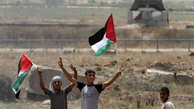 गज़ा में फलस्तीनी झंडे के साथ प्रदर्शन करते युवक