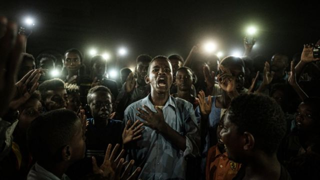 Un joven, iluminado por teléfonos móviles, recita un poema mientras los manifestantes cantan consignas pidiendo un gobierno civil, durante un apagón en Jartum (Sudán), el 19 de junio de 2019.