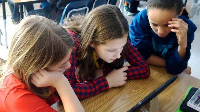 Meninas olham para tela de computador em sala de aula