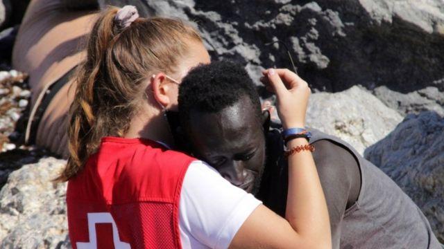 İspanyol Kızıl Haç üyesi bir göçmeni kucaklıyor