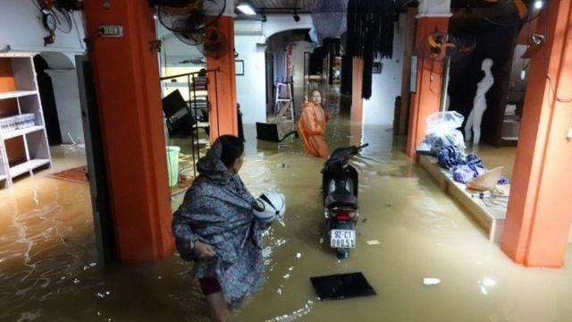 Local residents stand inside their flooded home in the tourist town of Hoi An, Vietnam (05 November 2017)