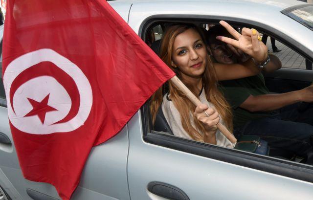 تونسية تلوح بالعلم من السيارة
