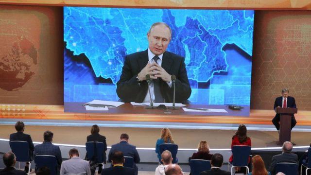 الرئيس فلاديمير بوتين يتحدث إلى الحضور عبر شاشة