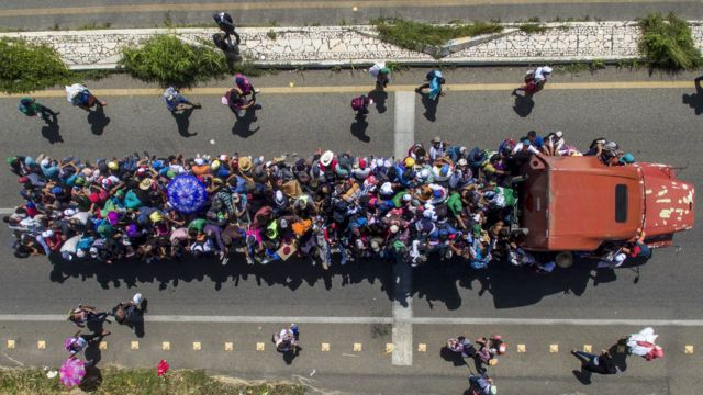 Image shows an eerial view of Honduran migrants onboard a truck as they take part in a caravan heading to the US