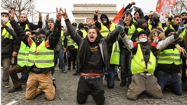 """Des """"gilets jaunes"""" font le signe de victoire, face aux policiers."""