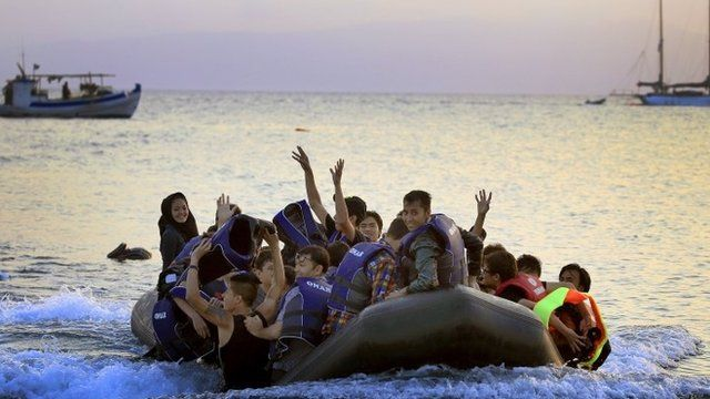 Afghan migrants rejoice on reaching the Greek island of Kos from Turkey by boat, on 9 August 2015