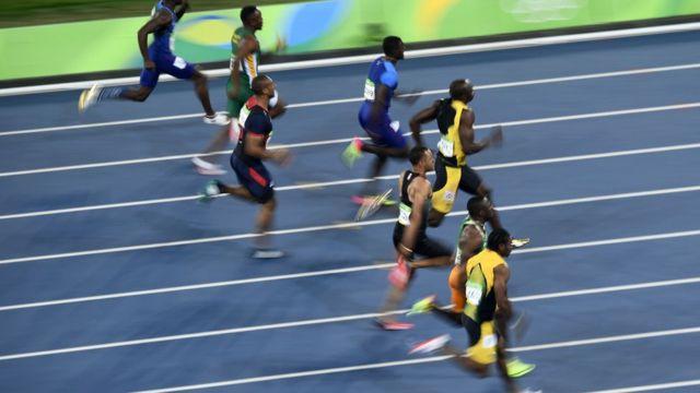 Usain Bolt com outros três competidores na prova dos 100 metros
