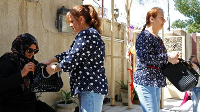 وفي العاصمة العراقية بغداد وتحديدا في حي الكرادة تخضع سيدة عراقية للتفتيش قبل السماح لها بدخول كنيسة العذراء مريم لحضور القداس