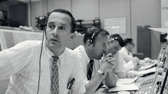 Personal en tierra sentados frente a consolas durante la misión del Apolo 11