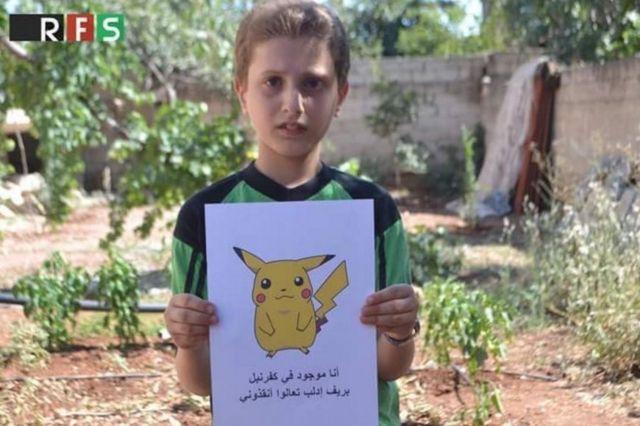 ポケモンの絵を掲げて助けを求めるシリアの少年