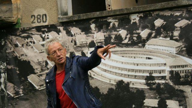 Guia local Bernd Redder em frente a imagem que mostra antigo restaurante do complexo