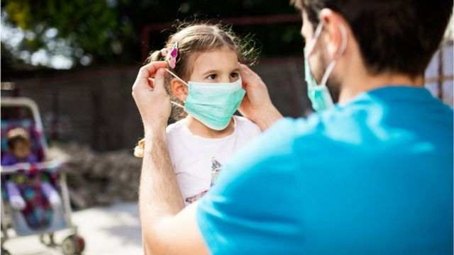 Pai ajusta máscara em rosto de filha