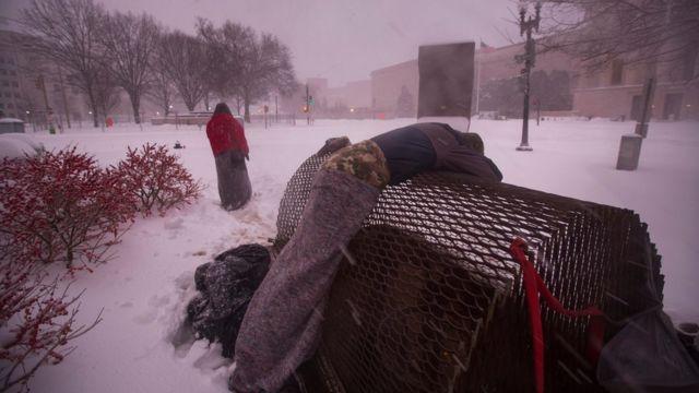 吹雪の中、鉄の囲いの上で休むホームレスの男性(23日)