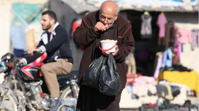رجل مسن يحمل بعض الطعام الذي يوزع في المدينة