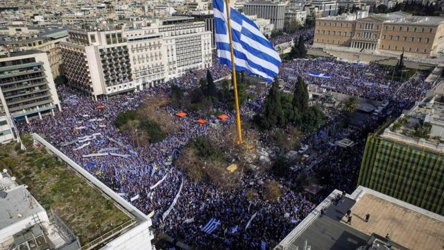 People hold Greek flags as they demonstrate to urge the government not to compromise in the festering name row with neighbouring Macedonia, at the Syntagma Square in Athens, on February 4, 2018